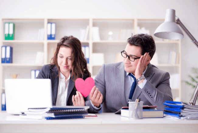 office man passing paper heart to female office worker