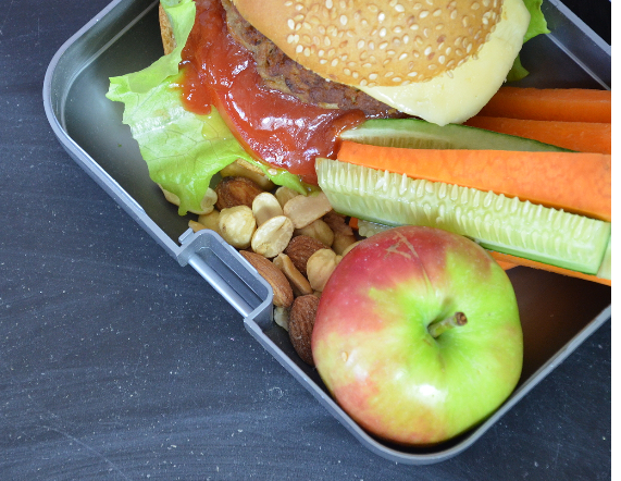 lunch box with sandwich, nuts and vegetables