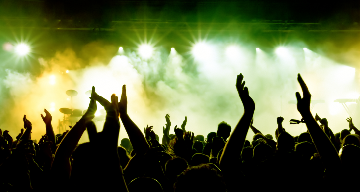 silhouettes of hands at a music festival stage