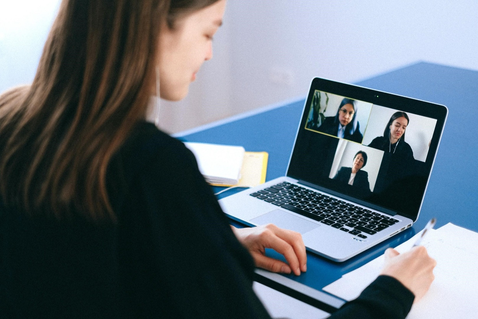 woman talking to colleagues via video call on a laptop
