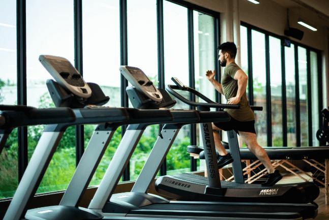 man running on a treadmill facing a window in a gym