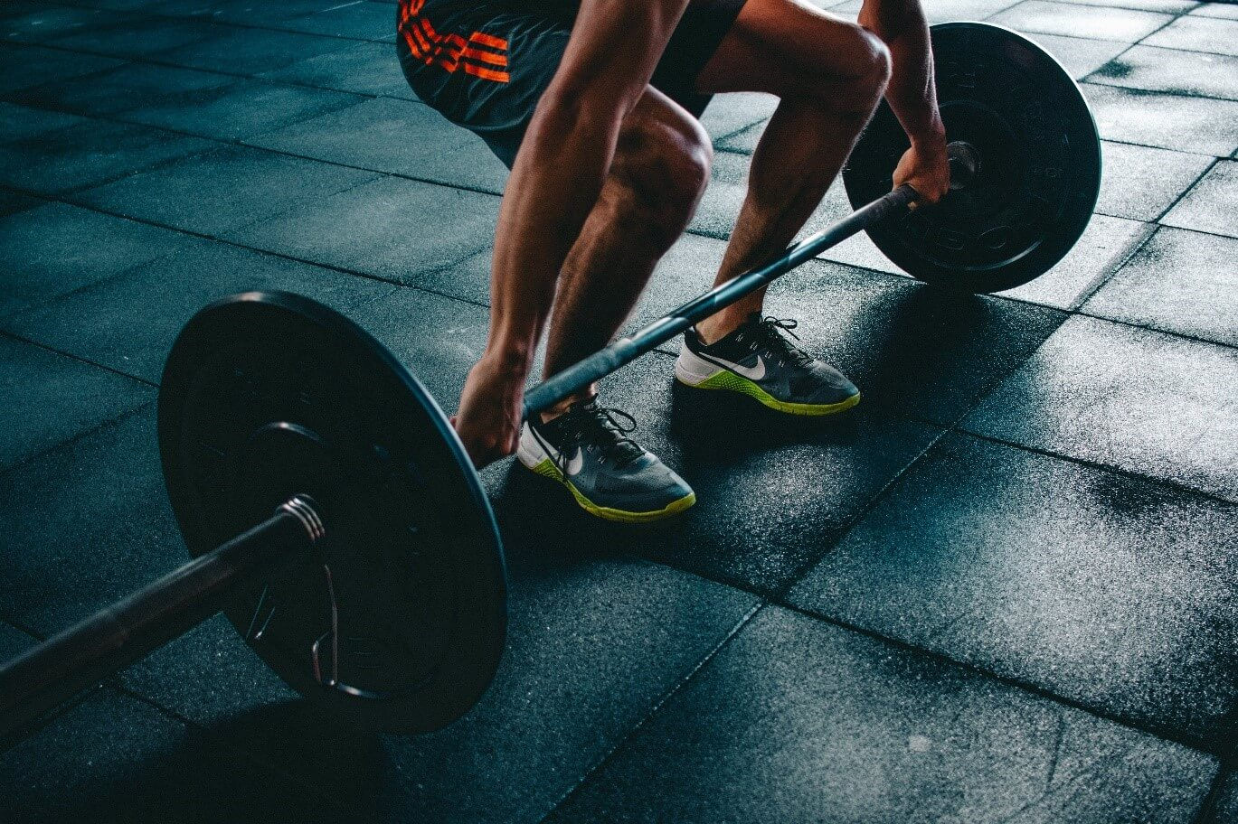 man in a gym lifting barbell weights