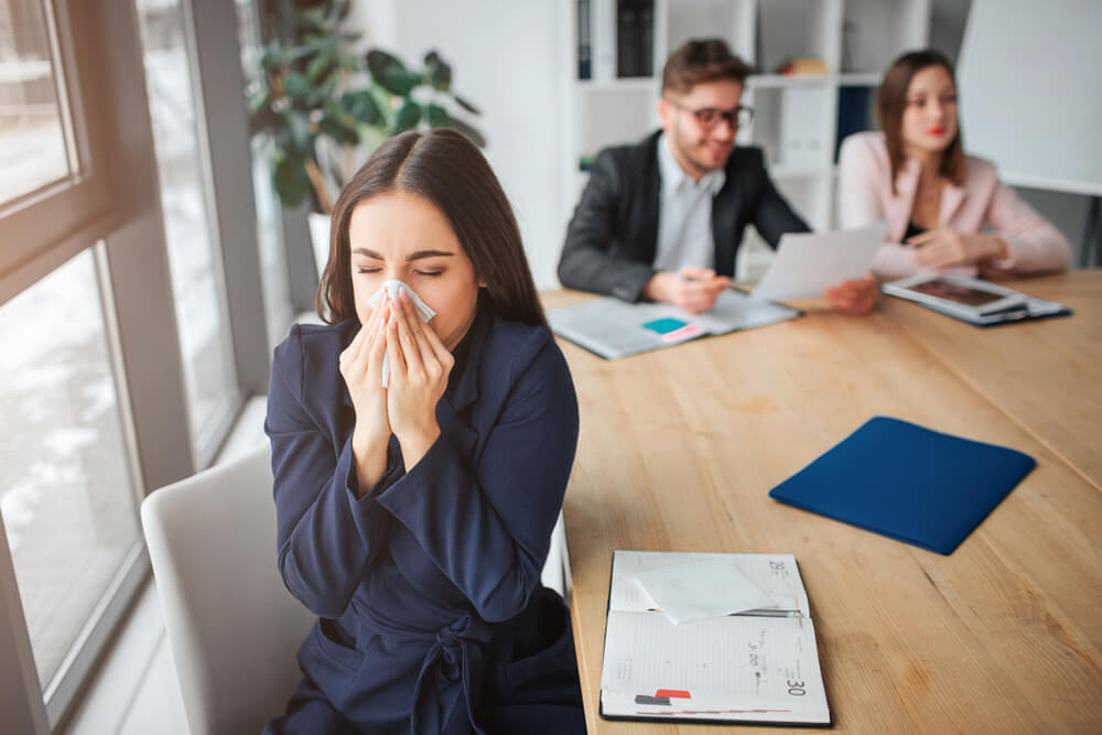 woman sneezing into a tissue in a work meeting