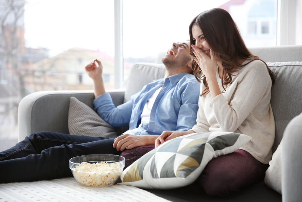 man and woman laughing and eating popcorn on a settee