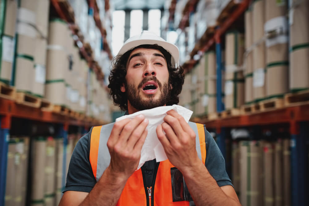 man in high vis jacket sneezing in a warehouse