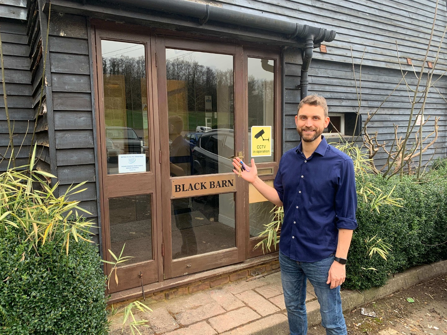 Simon Cornelius holding keys in front of new office space