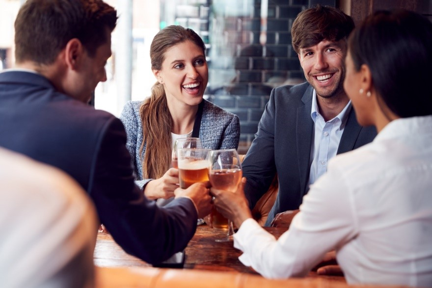 young professionals in a pub drinking beer and wine