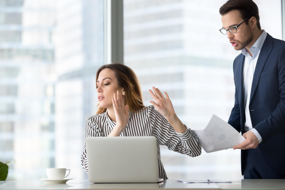 Woman holding hands up to stop man from talking at a desk